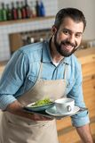 Positive responsible waiter smiling while taking the dirty dishes. Professional waiter. Attentive responsible cheerful waiter smiling while being at work and Royalty Free Stock Photography