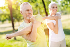 Positive retired couple stretching their hands. More sport. Positive smiling retired couple stretching their hands while doing sport exercises in the park Stock Images