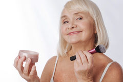 Positive retired woman using a makeup brush Stock Image
