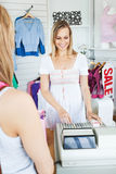 Positive saleswoman using the cash register. Positive saleswoman standing behind the counter using the cash register in a clothes store Royalty Free Stock Photography