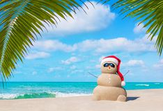 Sandy Snowman in Christmas Santa hat and sunglasses at palm beac. Positive sandy snowman in red Santa Claus hat and sunglasses at cloudy sunny ocean beach under Royalty Free Stock Photos