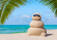 Positive sandy snowman in sunglasses at palm ocean sandy beach. Positive sandy snowman in black sunglasses and carrot nose at tropical ocean beach under palm Stock Photo