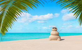 Positive sandy snowman in sunglasses at tropical ocean palm beach stock images