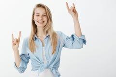 Positive schöne europäische Frau mit dem blonden Haar, Hände mit Felsengesten anhebend und nett lächeln und stehen Lizenzfreies Stockbild