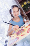 Positive school girl are painting at home Royalty Free Stock Photo