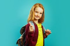 Positive schoolchild with backpack behind his shoulders shows his thumb, showing positive attitude to study, standing on royalty free stock photos
