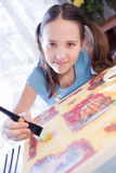 Positive schoold girl are painting at home Stock Image