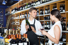 Positive seller man giving sample taste of wine. Positive seller men wearing apron giving sample taste of wine in glass to women customer in wine store Royalty Free Stock Photos