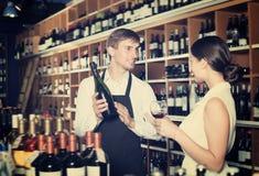 Positive seller man giving sample taste of wine. Positive seller men wearing apron giving sample taste of wine in glass to women customer in wine store Stock Image