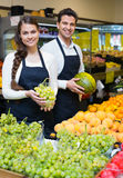 Positive sellers offering good price for fruits Royalty Free Stock Photo