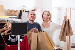 Positive senior couple with purchases in bags Stock Photos