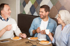 Positive senior couple resting with their grandson. Meet up for lunch. Cheerful handsome smiling men sitting at the table and drinking coffee with his Royalty Free Stock Photos