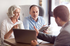 Positive senior couple talking with sales manager. Pleasant interaction. Positive senior couple sitting at the table and talking with sales manager Royalty Free Stock Photo