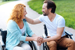 Positive senior disabled couple resting outdoors. Eternal love. Pleasant senior disabled couple expressing love and sitting in the wheelchairs while resting in Stock Photography