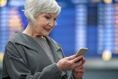 Positive senior female is holding mobile phone with smile. Sharing news. e view of optimistic elegant aged woman is standing in the airport and using smartphone Royalty Free Stock Photo