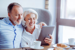 Positive senior loving couple resting in the cafe. Stay modern. Positive delighted loving couple sitting in the cafe and using tablet while expressing gladness Stock Photo