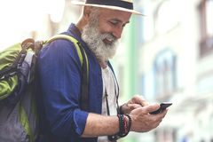 Positive senior male tourist using mobile phone. Portrait of cheerful old man searching for location with help of smartphone navigator. He is standing in city Stock Images