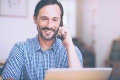 Positive senior man talking on smart phone Royalty Free Stock Image