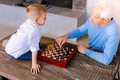 Positive senior man teaching his grandson to play chess Stock Photos