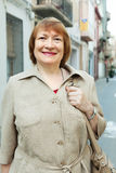 Positive senior woman at european city street Stock Photo