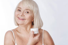 Positive senior woman fighting with wrinkles. Be always young. Pleasant positive elderly woman holding a bottle of anti age cream and smiling while fighting with Royalty Free Stock Images