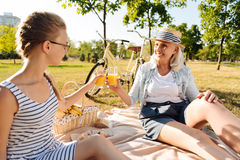 Positive senior woman and her granddaughter having a picnic Stock Photography