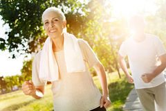 Positive senior woman jogging with her husband Stock Image