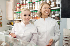 Positive senior woman selling pastry and nuts. Positive senior women selling pastry and nuts in shop stock images