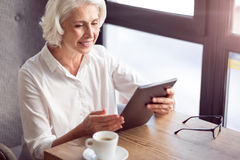 Positive senior woman sitting at the table. Modern way of communication. Positive delighted sitting at the table and using tablet while expressing gladness royalty free stock image