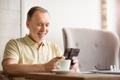 Positive senior woman using game console. Lets lay. Positive delighted senior man holding game console and playing while sitting at the table Royalty Free Stock Photos