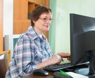 Positive senior woman using keyboard Royalty Free Stock Images