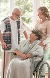 Positive senior woman on wheelchair with caring nurse and elderly friend with walking stick stock photos