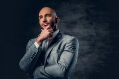 Positive shaved head male dressed in a grey suit. Positive shaved head male dressed in a grey suit over dark grey background Stock Photos
