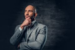 Positive shaved head male dressed in a grey suit. Positive shaved head male dressed in a grey suit over dark grey background Stock Images