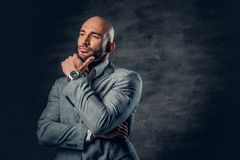 Positive shaved head male dressed in a grey suit. Positive shaved head male dressed in a grey suit over dark grey background Royalty Free Stock Photography