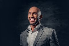 Positive shaved head male dressed in a grey suit. Positive shaved head male dressed in a grey suit over dark grey background Royalty Free Stock Photos