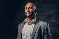 Positive shaved head male dressed in a grey suit. Positive shaved head male dressed in a grey suit over dark grey background Stock Photography