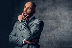 Positive shaved head male dressed in a grey suit. Positive shaved head male dressed in a grey suit over dark grey background Stock Image