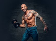 Positive shaved head shirtless male dressed in a jeans holds the. Dumbbell over dark grey background Stock Images