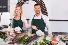 Positive shop assistants selling fresh fish Stock Photo