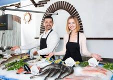 Positive shop assistants selling fresh fish Stock Photos