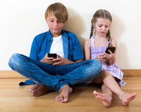Positive siblings playing with phones Stock Image