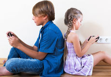 Positive siblings playing with phones Royalty Free Stock Photo