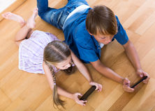 Positive siblings playing with phones Stock Images