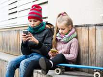 Positive siblings playing with phones on street Stock Image