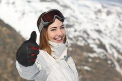 Positive Skifahrerfrau, die Daumen oben im Winter gestikuliert Stockbild