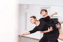 Positive slender woman being in hands of her dance partner stock image