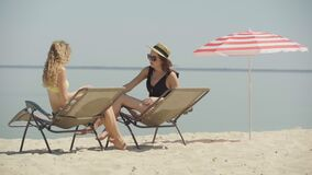 Positive slim young women rubbing sunscreen on tanned body on sandy beach. Portrait of confident young Caucasian