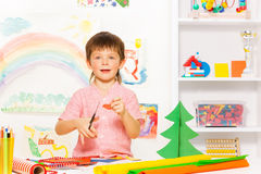 Positive small boy holding scissors and carton Royalty Free Stock Photos
