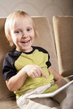 Positive small boy with tablet computer Stock Image